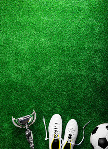 Soccer ball, cleats and trophy against artificial turf, studio shot on green background. Copy space.