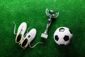 Soccer ball, cleats and trophy against artificial turf, studio shot on green background. Flat lay.