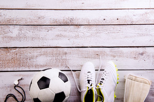 Soccer ball, cleats, protectors and whistle against wooden floor, studio shot on white background. Flat lay, copy space