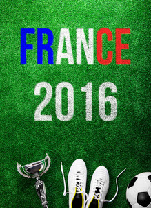 Soccer ball, cleats, trophy and France 2016 sign against artificial turf. Studio shot on green background. Flat lay.