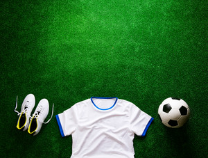 Soccer ball, cleats, white t-shirt against artificial turf. Studio shot on green background. Flat lay. Copy space.