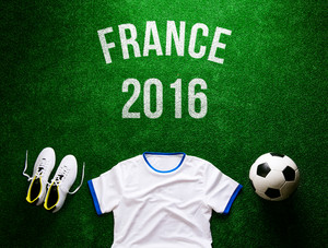 Soccer ball, cleats, white t-shirt and France 2016 sign against artificial turf. Studio shot on green background.