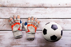 Soccer ball, gloves against wooden floor, studio shot on white background. Flat lay, copy space