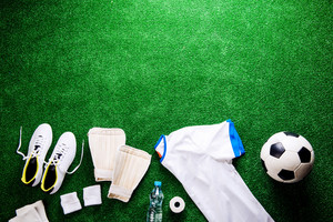 Soccer ball,cleats and various football stuff against artificial turf. Studio shot on green background. Copy space.