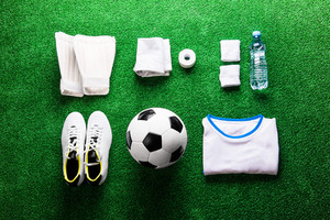 Soccer ball,cleats and various football stuff against artificial turf. Studio shot on green background. Flat lay, knolling.