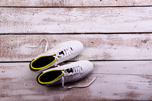Soccer cleats against wooden floor, studio shot on white background. Copy space.