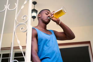 Social issues and substance abuse. Alcoholic young black man drinking alchool from liquor bottle at home, looking at camera