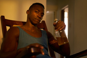 Social issues, substance abuse with alcoholic young black man drinking alchool from liquor bottle at home, looking at camera holding bottle of whiskey.