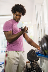 Sport and fun, young african american male athlete taking weights from shelf in fitness club