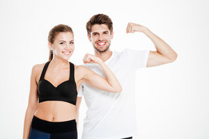 Sport couple standing and showing biceps together isolated on a white background