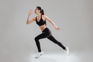 Sporting woman running in studio. Side view. Isolated gray background