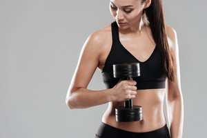 Sporting woman using dumbbell in studio. Isolated gray background