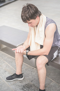 Sportive young handsome brown hair man checking his heart beats with his wristwatch, looking downward, with a towel around his neck - sportive, healthy, fitness concept