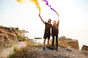 Sports couple with smoke bomb in hands standing together outdoors at the seaside and looking away