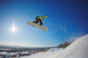 Sportsman snowboarding in winter against blue sky