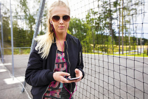 Sporty Woman Holding Mobile Phone While Listening Music By Fence