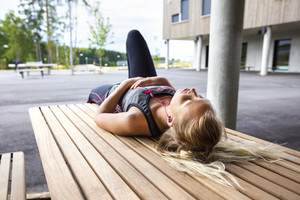 Sporty Woman Listening Music While Resting On Bench
