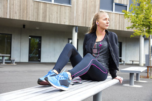 Sporty Woman Listening To Music While Sitting On Bench