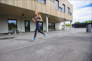 Sporty Young Woman Running By Building
