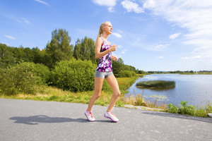 Sporty young woman runs on road along the water