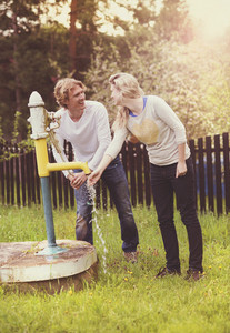Spring outdoor portrait of young happy couple pumping water from water pump