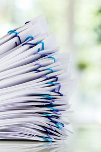 Stack of documents organized with paper clips in an office
