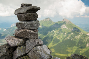Stack of rocks stones with cloudy mountains after rain, rainy misty day, High Tatras, Slovakia.  Beautiful mountain landscape.