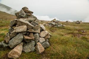 Stacks of rocks stones with cloudy mountains after rain, rainy misty day, High Tatras Slovakia.  Beautiful mountain landscape.