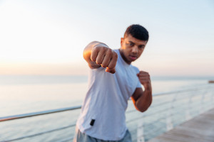 standing and doing boxing training on pier
