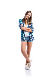 Standing teenage girl in denim shorts , tight singlet, blue checked shirt and canvas sneakers, arms crossed, young woman, isolated on white background