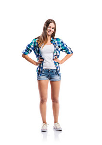 Standing teenage girl in denim shorts , tight singlet, blue checked shirt and canvas sneakers, arms on hips, young woman, isolated on white background