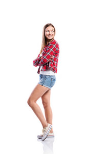 Standing teenage girl in denim shorts , tight singlet, red checked shirt and canvas sneakers, arms crossed, young woman, isolated on white background