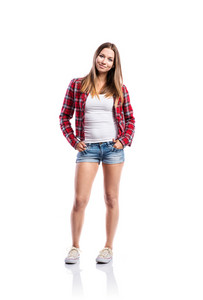 Standing teenage girl in denim shorts, tight singlet, red checked shirt and sneakers, hands in the pockets, young woman, isolated on white background
