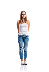 Standing teenage girl in jeans, tight singlet and sneakers, hands holding behind back, young woman, isolated on white background