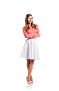 Standing teenage girl in pink lace top and elegant white skirt, heels, arms crossed, studio shot, young woman, isolated on white background
