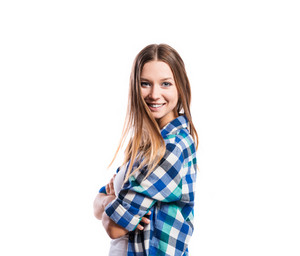 Standing teenage girl in tight singlet and blue checked shirt, arms crossed, young woman, isolated on white background