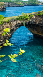 Stone arch over the sea. Broken beach. Rock coastline. Nusa Penida, Indonesia.