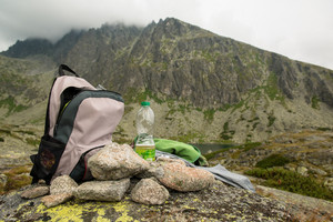 Stones, backpack and water bottle. Foggy and cloudy mountains after rain, rainy misty day, High Tatras Slovakia.  Beautiful mountain landscape.