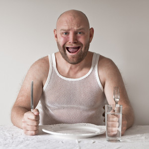 Strange and hungry man with no food on his plate. Perhaps on a diet?