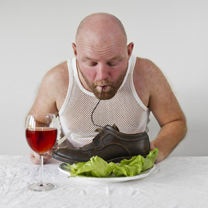 Strange man eat his shoes with a salad. Eat shoelaces as spaghetti.