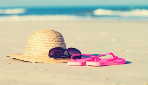 Straw hat and sunglasses on a tropical beach