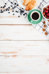Strawberry, blueberries, nuts, croissants and cup of coffee on wooden background