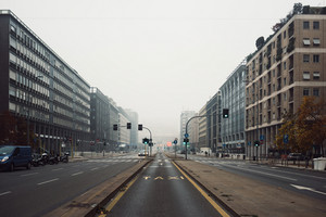 Street front view of Milano Centrale railway station in a foggy day with no traffic