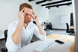 Stressed young businessman touching his temples and having a headache in office