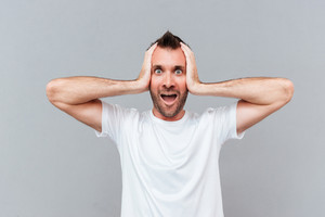 Stressed young man covers ears by hands and shouting over gray background