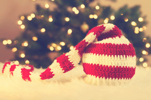 Striped Santa Hat on white carpet in front of tree