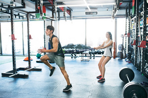 Strong man using a resistance band in his exercise routine. Young fit couple performs fitness exercise in modern crossfit gym.