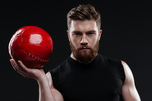 Strong man with ball. close up portrait. isolated dark background