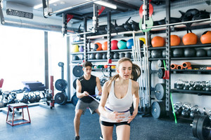 Strong woman using a resistance band in her exercise routine. Young fit couple performs fitness exercise in modern crossfit gym.