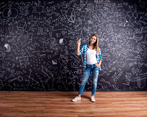 Student holding a chalk, against big blackboard with mathematical symbols and formulas. Studio shot on black background.